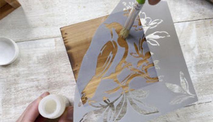 Опустите трафаретную кисть в клей и сразу начинайте покрывать им трафарет, совершая движения кистью «вверх» и «вниз». Важно работать быстро, потому что клей начнет проникать в древесину.