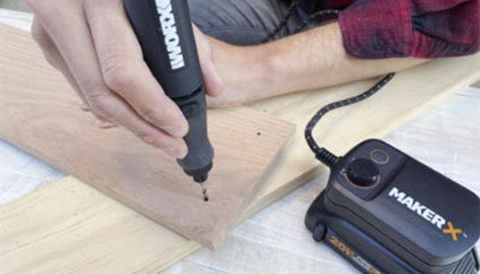 Положите кусок древесины и возьмите гравировальную машинку WORX WX739.9                         20V с насадкой для сверления. Подключите ее к одному из специальных адаптеров. С помощью инструмента проделайте четыре отверстия.
