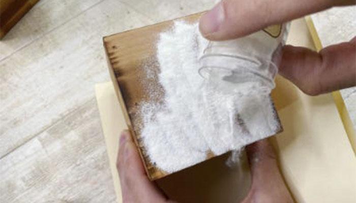 Очистите трафарет и насыпьте нужное количество порошка для тиснения на сторону ящика. промазанную клеем. После того, как она будет полностью покрыта порошком, стряхните излишки порошка на клочок бумаги.