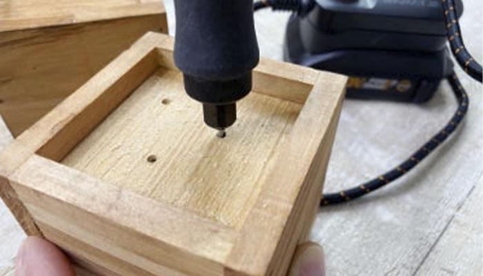 Прикрепите насадку для сверления к гравировальной машинке WORX WX739.9 20V и подключите прибор к одному из специальных адаптеров. Возьмите деревянный ящик и просверлите три-четыре дренажных отверстия в нижней его части,                 сделайте так для каждого ящика.